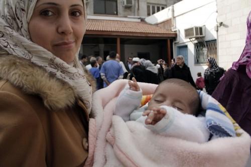 Una mujer musulmana y su bebé esperan por una revisión médica en el hospital Al Ahli Arab de la Ciudad de Gaza el 2 de enero. El hospital dirige un programa de tres meses para niños desnutridos. Foto de Lynette Wilson para ENS.