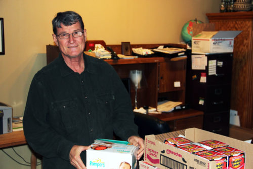 Bill Fojtasek prepares care packages to ship to service members in Afghanistan. Photo/Mike Patterson