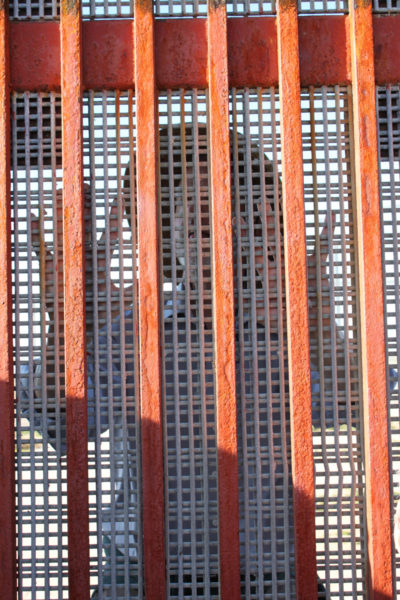 """Heavy metal mesh placed over the grid of the wall in """"Friendship Park"""" prevents all physical contact and most visual contact between the U.S. and Mexican sides of the border. Some 50 feet away on the U.S. side is a second fence that is opened only for brief periods on weekends to allow those on either side of the wall to talk to their families and friends on the other side. Photo: Janet Kawamoto"""