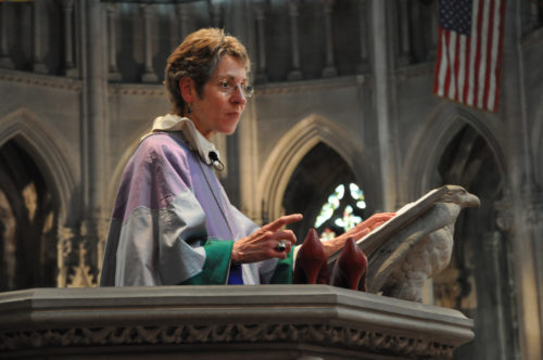 Presiding Bishop Katharine Jefferts Schori during her sermon at Church of the Advocate uses a pair of red high heels to illustrate the expectations set upon ordained women. Photo: Mary Frances Schjonberg/Episcopal News Service