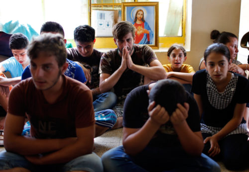 Displaced Iraqi Christians who fled from Islamic State militants in Mosul, pray at a school acting as a refugee camp in Erbil. Photo: REUTERS/Ahmed Jadallah